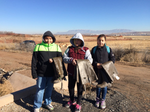 Truman Middle School students begin a day of water quality testing at the Valle de Oro National Wildlife Refuge by carrying waders into the Rio Grande bosque.