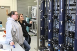 Ezzie Sauter Baca, water treatment technician (left), and Andrea Song, water treatment engineer (right), discuss an experiment using the pilot treatment plant's replica filters. The filter tubes are filled with anthracite and granular activated carbon to strain out particles from the water.