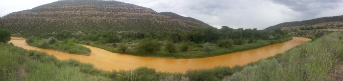 The orange plume flows through the Animas across the Colorado/New Mexico state line the afternoon of Aug. 7, 2015. (Photo by Melissa May, San Juan Soil and Conservation District)
