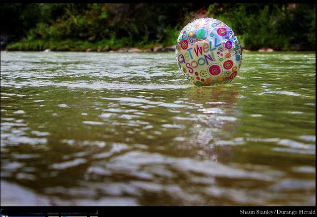"A ""get well soon"" balloon floats in the contaminated waters of the Animas River flowing through Durango on Monday afternoon -- photo The Durango Herald, Shane Benjamin"
