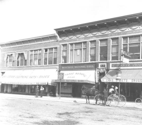 "View along Main Street in early Montrose (between 1905 and 1915). Shows a horse-drawn carriage, bicycles, and two men talking. Signs include: ""The Humphries  Mercantile Co. Dry Goods, Clothing, Hats & Shoes"" ""Montrose National Bank"" and C. J. Getz, Pharmacist, Druggist."" via http://photoswest.org"
