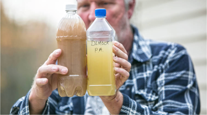 Ray Kemble holds two samples of well water from his neighborhood in Dimock, PA. He says the water was contaminated after fracking. - Amanda Hrycyna for APM Reports
