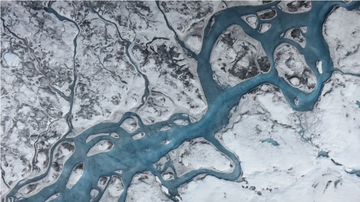 Rivers of meltwater and a mantle of soot, dust, and microbes darken the surface and speed melting. Surface melting has now surpassed the discharge of icebergs into the ocean as a major cause of ice loss. Photo credit Marco Tedesco/Lamont-Doherty Earth Observatory.
