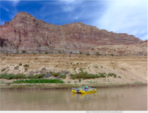 "A raft floats past silt walls left on the Colorado River and revealed by dropping levels in Lake Powell, in October 2016. A ""risk study"" being undertaken by west slope water interests wants to know who might have to someday divert less water to keep Lake Powell operational. Photo credit Brent Gardner-Smith."