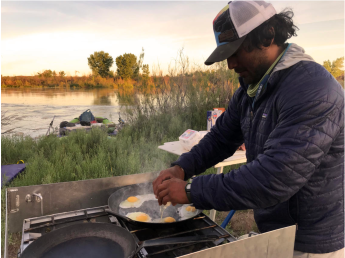 Austin Alvarado cracks eggs into a sizzling pan for breakfast sandwiches. (Public domain.)